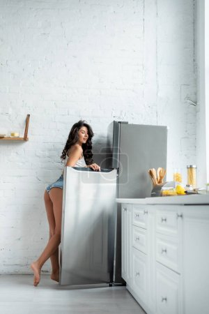 Photo for Side view of sexy woman standing near open fridge in kitchen - Royalty Free Image