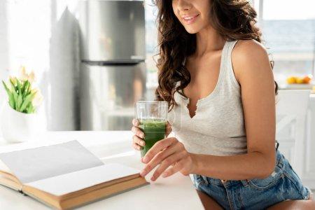 Ausgeschnittene Ansicht eines lächelnden Mädchens, das Buch liest und ein Glas Smoothie auf dem Küchentisch hält