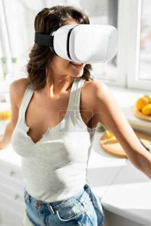 Photo for Smiling woman using virtual reality headset in kitchen - Royalty Free Image