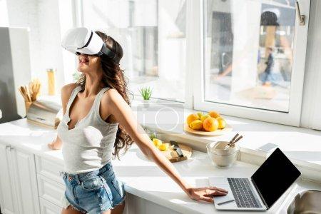 Photo pour Jeune femme en short en denim sortant la langue tout en utilisant un casque vr près d'un ordinateur portable et une carte de crédit dans la cuisine - image libre de droit