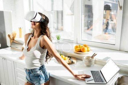 Photo pour Jeune femme en short en denim chanter casque vr près d'un ordinateur portable et carte de crédit sur le plan de travail de la cuisine - image libre de droit