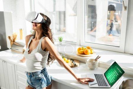 Photo pour Femme utilisant un casque de réalité virtuelle près d'un ordinateur portable et une carte de crédit dans la cuisine - image libre de droit