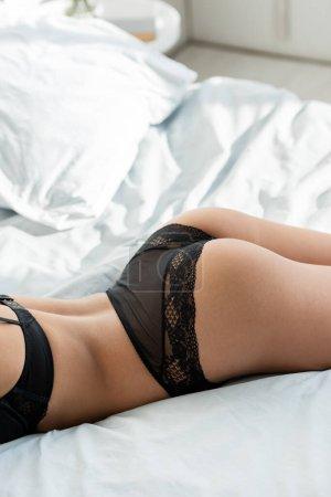 Photo pour Vue recadrée de la femme sensuelle en soutien-gorge et culotte couché sur le lit - image libre de droit