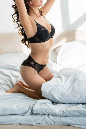 Photo pour Vue recadrée de femme sexy en soutien-gorge et culotte assis sur le lit - image libre de droit