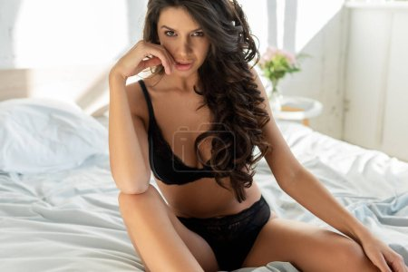 Photo pour Femme sensuelle en soutien-gorge et culotte regardant la caméra sur le lit - image libre de droit