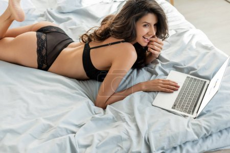 KYIV, UKRAINE - MARCH 13, 2020: high angle view of sexy girl with laptop smiling and lying on bed in bedroom