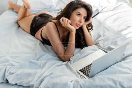 Photo for Thoughtful and sexy woman with credit card lying near laptop on bed in bedroom - Royalty Free Image