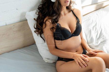 Photo pour Vue recadrée de fille chaude en lingerie sur le lit dans la chambre - image libre de droit