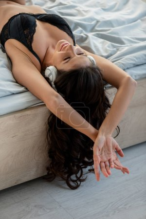 Photo for Sexy woman in headphones smiling and resting on bed in bedroom - Royalty Free Image