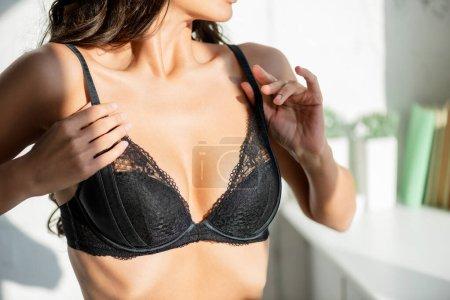 Photo pour Vue recadrée de femme sexy toucher soutien-gorge dans la chambre - image libre de droit