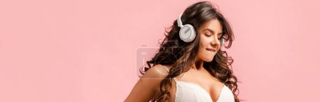 Photo for Panoramic orientation of sexy girl with headphones biting lip isolated on pink - Royalty Free Image