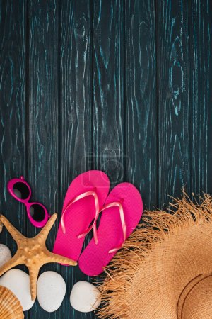 Photo for Top view of pink flip flops near sunglasses, starfish and sea stones on dark wooden background - Royalty Free Image
