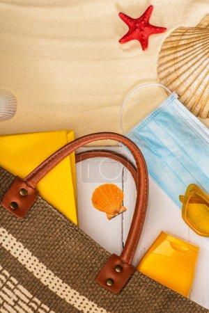 Vue du dessus du masque médical près de la crème solaire, sac et livre sur des planches de bois blanc près des coquillages sur le sable