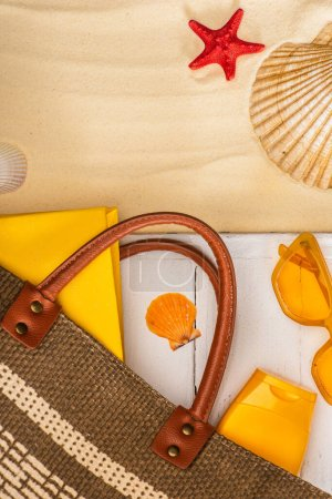 Photo for Top view of bag, sunscreen and book on white wooden planks near seashells on sand - Royalty Free Image