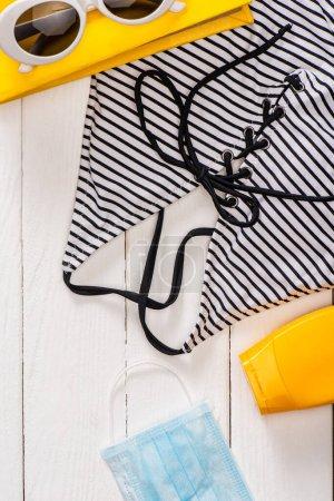 Photo pour Vue du dessus de maillot de bain dépouillé, lunettes de soleil près du livre et masque médical sur fond de bois blanc - image libre de droit