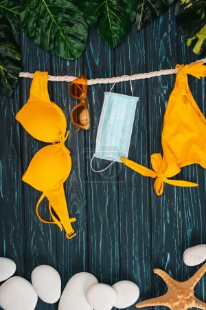 Photo for Top view of yellow swimsuit near medical mask, sunglasses and leaves on dark wooden surface - Royalty Free Image