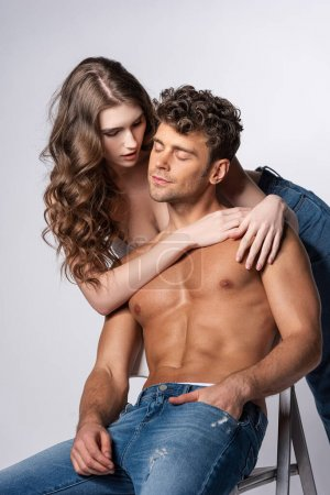 Photo for Attractive young woman touching shirtless man in jeans sitting with hand in pocket on grey - Royalty Free Image