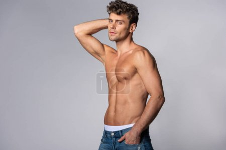 Photo for Shirtless man in denim jeans standing with hand in pocket on grey - Royalty Free Image