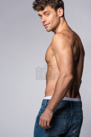 Photo for Muscular man in blue denim jeans standing isolated on grey - Royalty Free Image
