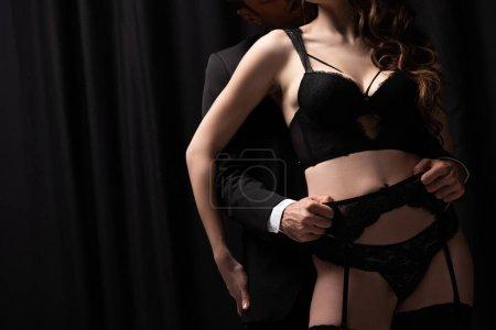 Photo pour Vue recadrée de l'homme en costume touchant femme séduisante en sous-vêtements et bas sur noir - image libre de droit