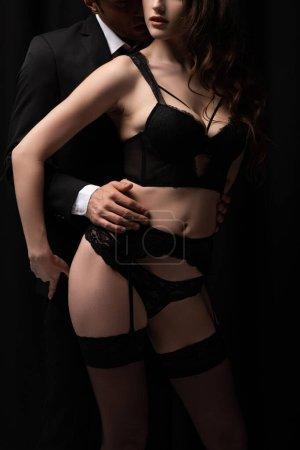 Photo pour Vue recadrée de l'homme en costume touchant femme sexy en sous-vêtements et bas isolés sur noir - image libre de droit