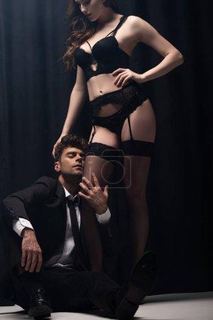 Photo pour Bel homme en costume toucher jambe de femme sexy en bas et assis sur noir - image libre de droit