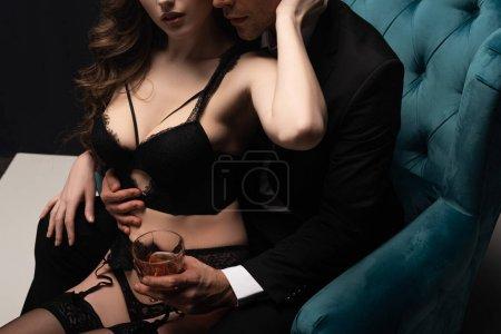 Photo pour Vue recadrée de femme sexy en lingerie assis sur bel homme avec un verre de whisky - image libre de droit