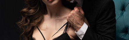 Photo for Panoramic shot of man touching bra of sexy woman isolated on black - Royalty Free Image