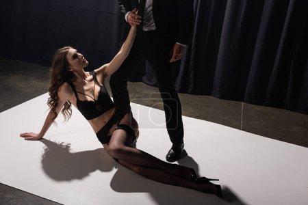 Photo pour Séduisante femme en lingerie noire couchée sur le sol et touchant homme en costume - image libre de droit