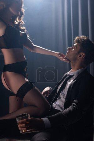 Photo pour Séduisante fille toucher le visage de l'homme en costume assis et tenant un verre de whisky sur noir - image libre de droit