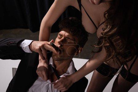Photo pour Femme passionnée en sous-vêtements touchant bel homme en costume fumant cigare - image libre de droit