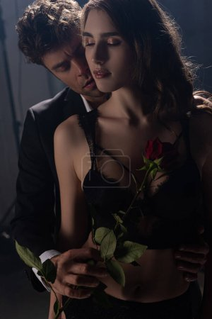 Photo for Passionate man holding red rose near woman in underwear on black - Royalty Free Image