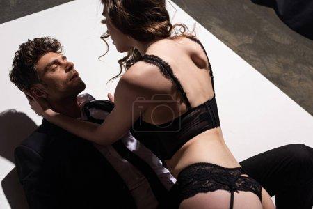 Photo pour Séduisante femme en lingerie sexy en regardant bel homme en costume - image libre de droit