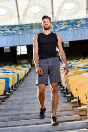 Photo for Young sportsman walking on stairs at stadium - Royalty Free Image