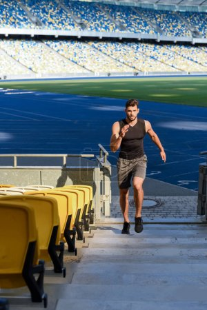 Photo for Young sportsman running on stairs at stadium - Royalty Free Image
