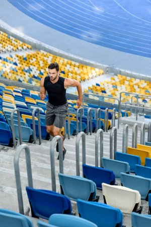 young sportsman running on stairs at stadium