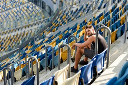 Photo for Young sportsman sitting on stairs near seats at stadium - Royalty Free Image