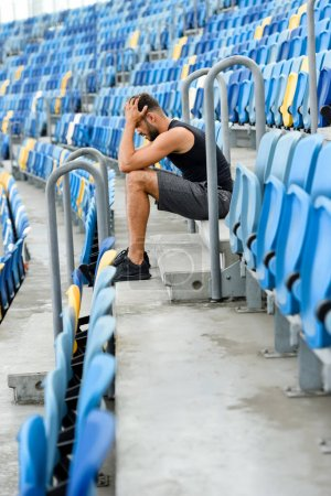 Photo for Side view of young sportsman holding head while sitting on stairs near seats at stadium - Royalty Free Image