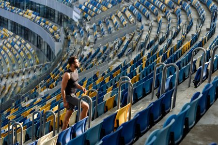 Photo for Young sportsman walking on stairs among seats at stadium - Royalty Free Image