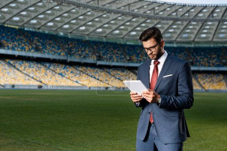 young businessman in suit and glasses using digital tablet at stadium