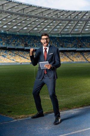 Photo pour Jeune homme d'affaires en costume et lunettes en tablette numérique montrant un geste d'amitié au stade, concept de paris sportifs - image libre de droit