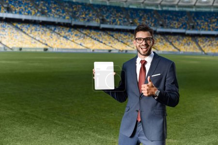 happy young businessman in suit and glasses holding digital tablet with blank screen and showing thumb up at stadium