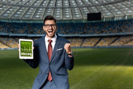 Photo for Cheerful young businessman in suit and glasses holding digital tablet with healthcare app and showing yes gesture at stadium - Royalty Free Image