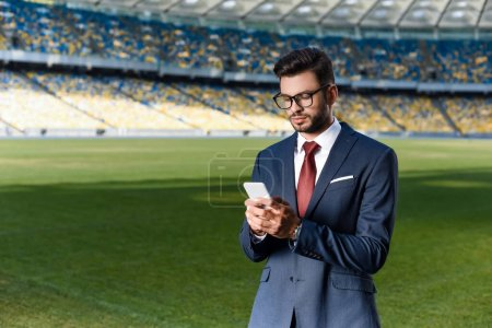 Photo for Young businessman in suit and glasses using smartphone at stadium - Royalty Free Image