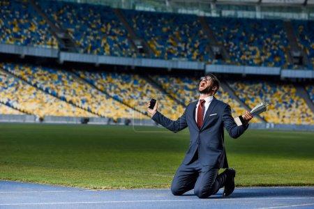 Photo pour Jeune homme d'affaires en costume debout sur les genoux avec smartphone et trophée au stade, concept de paris sportifs - image libre de droit