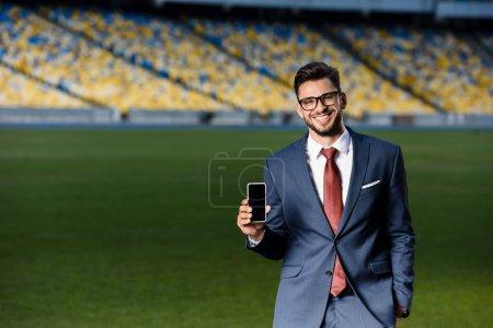jeune homme d'affaires souriant en costume et lunettes tenant smartphone avec écran blanc au stade