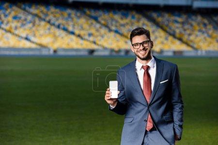 Photo pour Jeune homme d'affaires souriant en costume et lunettes tenant smartphone avec écran blanc au stade - image libre de droit