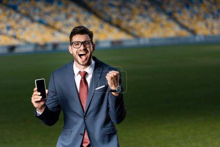 Photo pour Excité jeune homme d'affaires en costume et lunettes tenant smartphone avec écran blanc et montrant geste oui au stade - image libre de droit