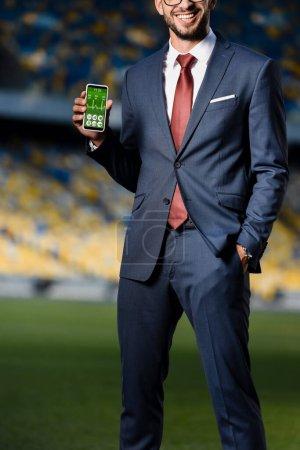 Photo pour Vue recadrée du jeune homme d'affaires en costume avec main dans la poche tenant smartphone avec application de soins de santé au stade - image libre de droit