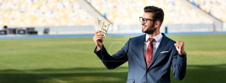 Foto de Sonriente joven empresario en traje y gafas con dinero que muestra el gesto de las yeas en el estadio, tiro panorámico. - Imagen libre de derechos